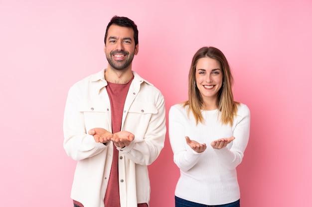 Paare in valentine day über lokalisierter rosa wand, die copyspace eingebildet auf der palme hält, um eine anzeige einzufügen