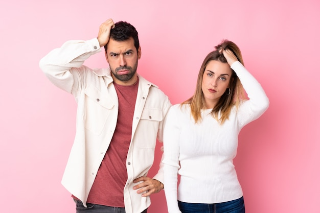 Paare in valentine day über lokalisierter rosa wand mit einem ausdruck der frustration und des nichtverständnisses