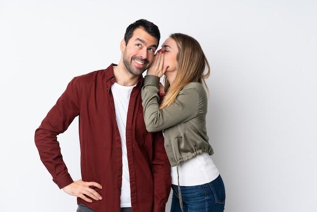 Paare in valentine day über lokalisierter wand, die etwas flüstert
