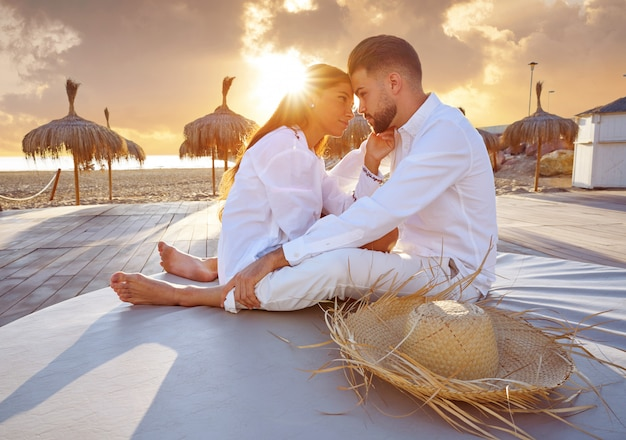 Paare jung im strandferiensonnenaufgang