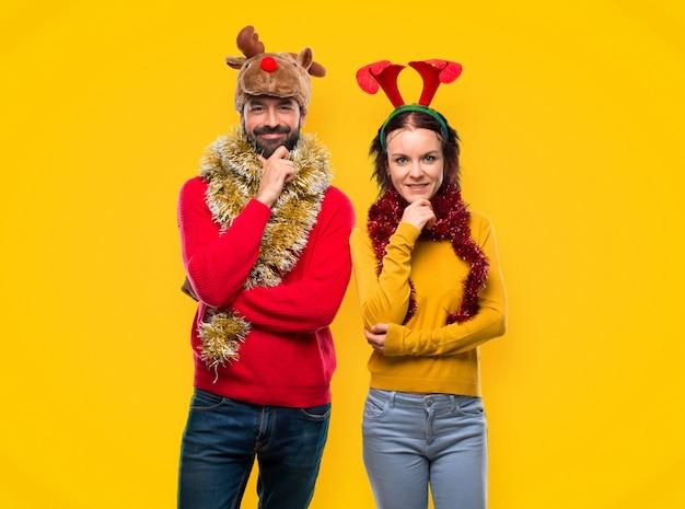 Paare kleideten oben für die weihnachtsfeiertage an und lächelten und schauen zur front mit vertrauen