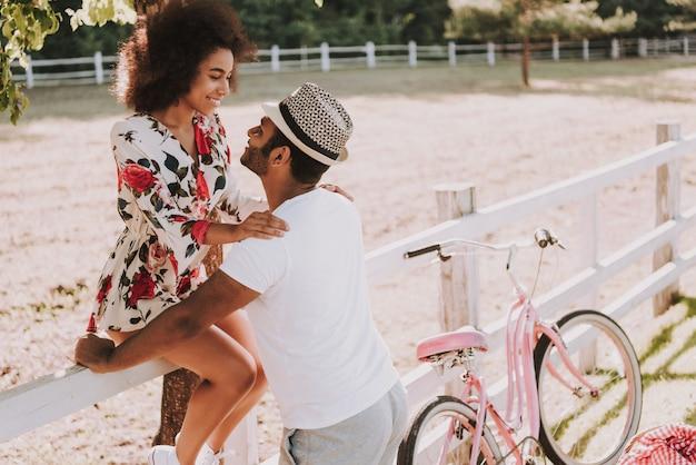Paare lehnen sich auf rennstrecke-zaun bike ride