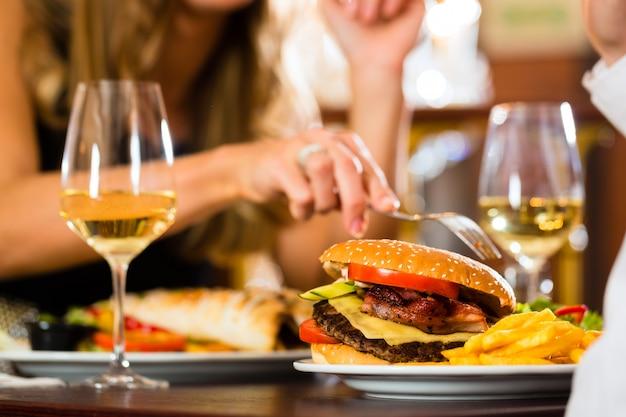 Paare, mann und frau ein feines speisendes restaurant, das sie schnellimbiß, burger und fischrogen, nahaufnahme essen