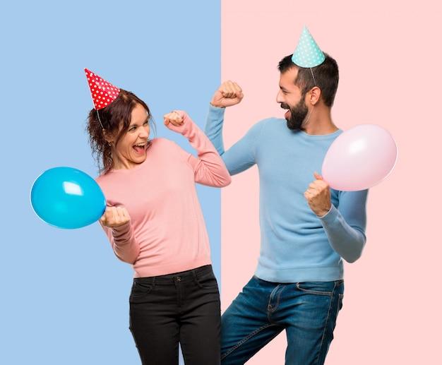 Paare mit ballonen und geburtstagshüten, die einen sieg in der siegerposition feiern