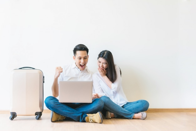 Paare mit dem laptop, der erfolgreiche planungsurlaubsreise feiert
