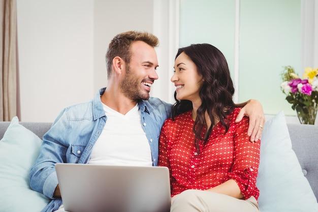 Paare mit dem laptop, der zu hause auf sofa stationiert
