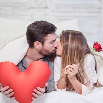 Paare mit dem spielzeugherzen, das auf bett küsst