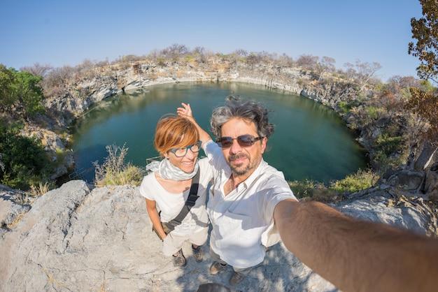 Paare mit den ausgestreckten armen, die selfie am otjikoto see, einer der nur zwei dauerhaften natürlichen see in namibia, afrika nehmen. konzept des abenteuers und der reisenden leute.