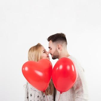 Paare mit den ballonen, die nasen berühren