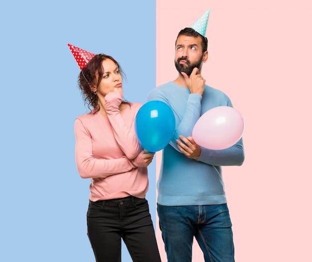Paare mit den ballonen und geburtstagshüten, die eine idee auf rosa und blauem hintergrund denken