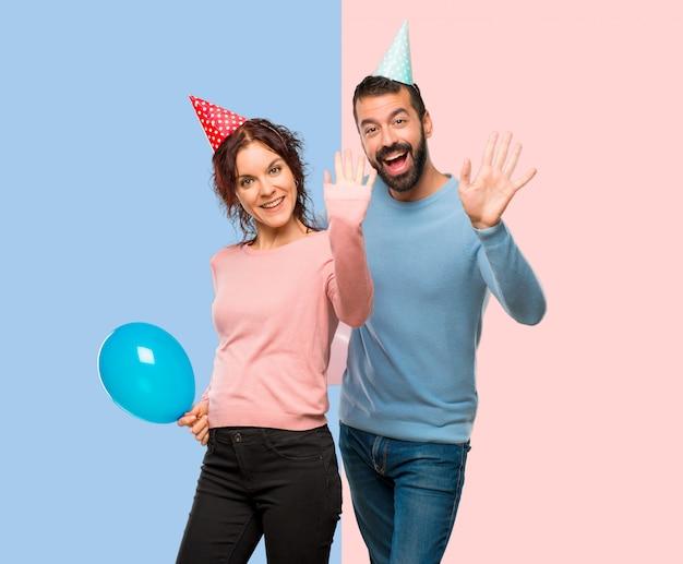 Paare mit den ballonen und geburtstagshüten, die mit der hand mit glücklichem ausdruck begrüßen