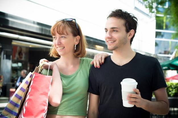 Paare mit den einkaufstaschen, die auf die straßen gehen.