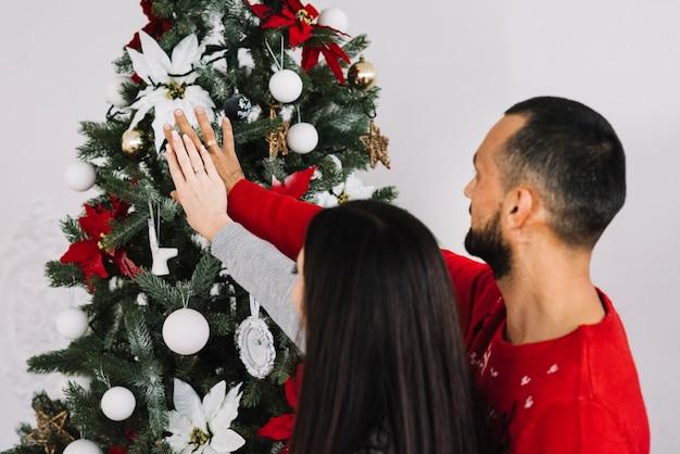 Paare mit den händen nähern sich weihnachtsbaum