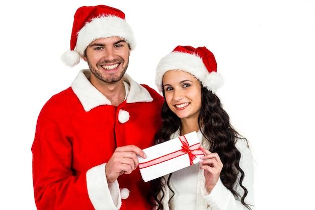Paare mit den weihnachtshüten, die geschenkbox halten