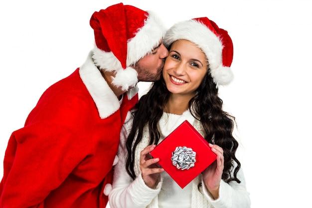 Paare mit den weihnachtshüten, die rote geschenkbox halten