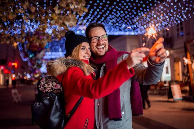 Paare mit den wunderkerzen, die weihnachtsfest in der stadtstraße genießen.