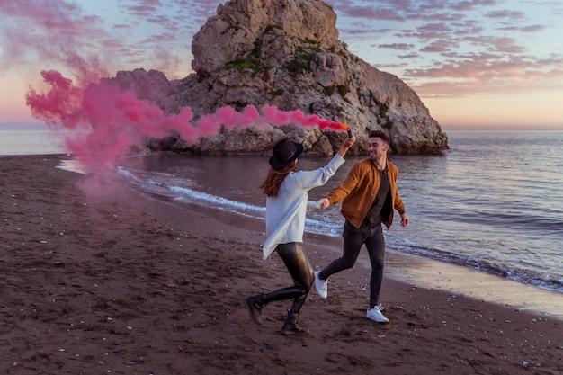 Paare mit der rauchbombe, die auf seeufer läuft