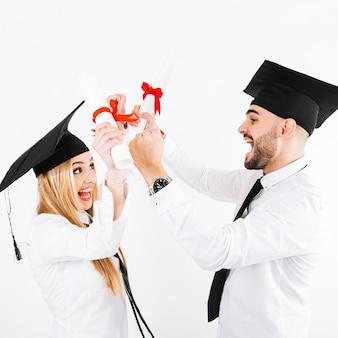 Paare mit diplomen, die spaß haben
