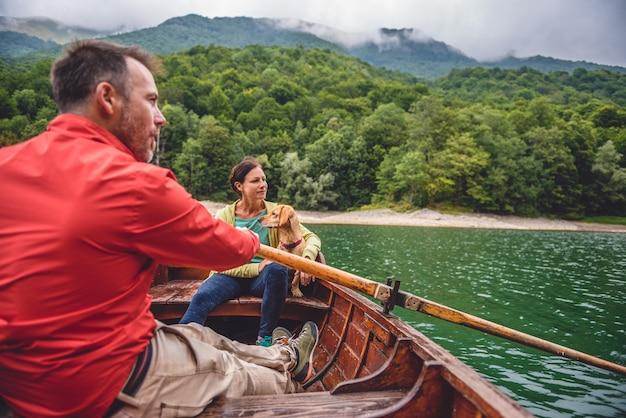 Paare mit einem hund, der ein boot auf einem see rudert