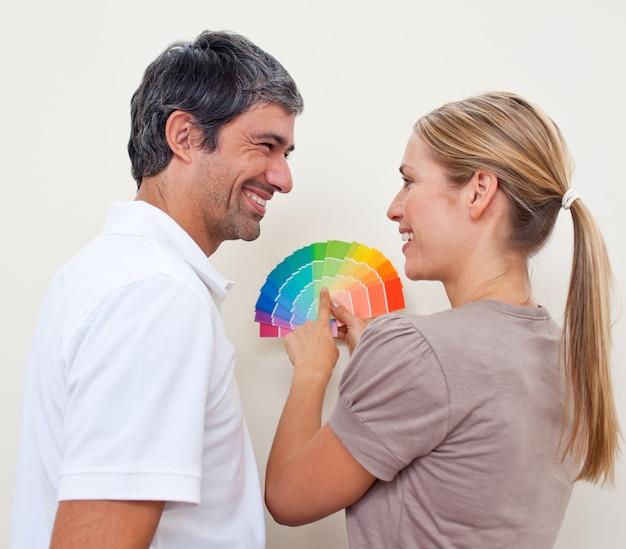 Paare mit farbproben, um ihre neue wohnung zu malen