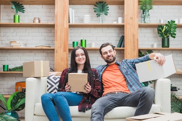 Paare mit paketen auf sofa