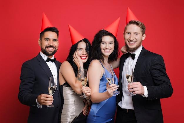 Paare mit partyhüten und champagner