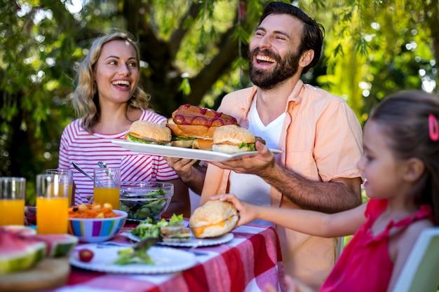 Paare mit sandwichen bei tisch im yard