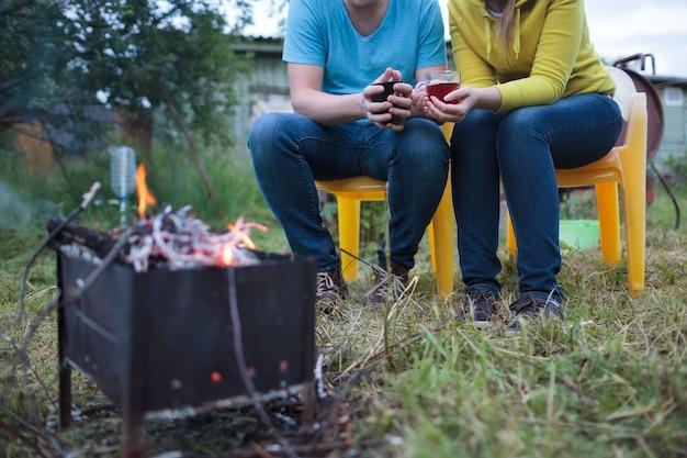 Paare mit teeschalen in den händen nahe dem schwelenden feuer
