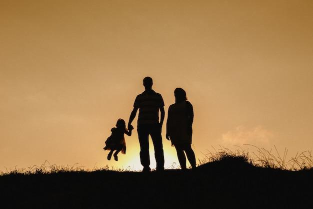 Paare mit wolkenhimmelhintergrundbeleuchtung