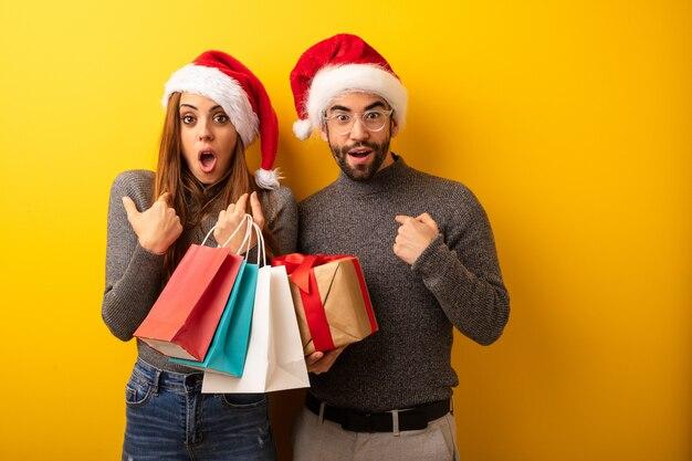 Paare oder freunde, die geschenke und einkaufstaschen überrascht halten, fühlt sich erfolgreich und wohlhabend