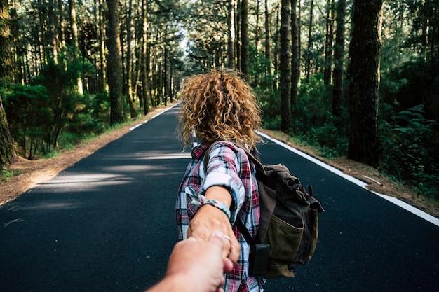 Paare reisen zusammen mit rucksack in einem wald auf einer langen asphaltstraße asphalt