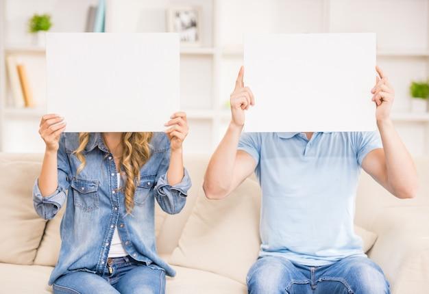 Paare schließen ihre gesichter mit leeren plakaten.