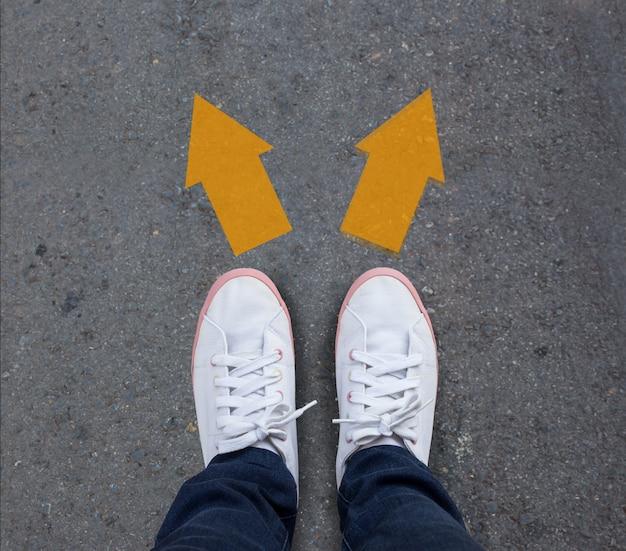 Paare schuhe, die auf einer asphaltstraße mit zwei pfeilen stehen