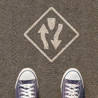 Paare schuhe, die auf einer straße mit verkehrszeichen stehen
