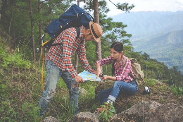 Paare sehen eine karte in einem tropischen wald mit rucksäcken im wald. abenteuer, wandern, klettern.