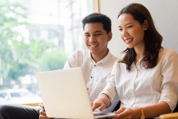 Paare sitzen auf couchsofa und spielen auf laptop zusammen am wohnzimmer in der freizeitwochenendenzeit