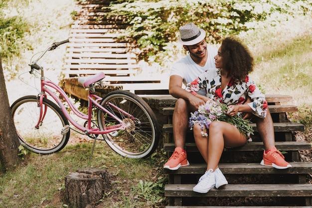 Paare sitzen auf hölzerner treppe im holz zusammen