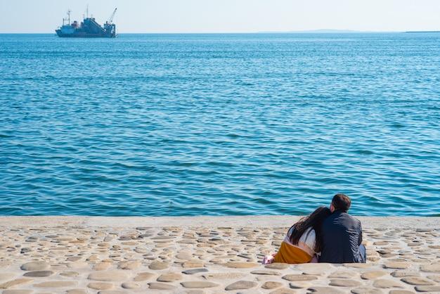 Paare sitzen auf ufer durch kaspisches meer in baku