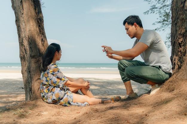 Paare sitzen zusammen herein auf dem strand unter der baumkiefer.