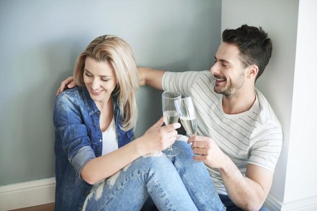 Paare teilen champagner während des umzugs