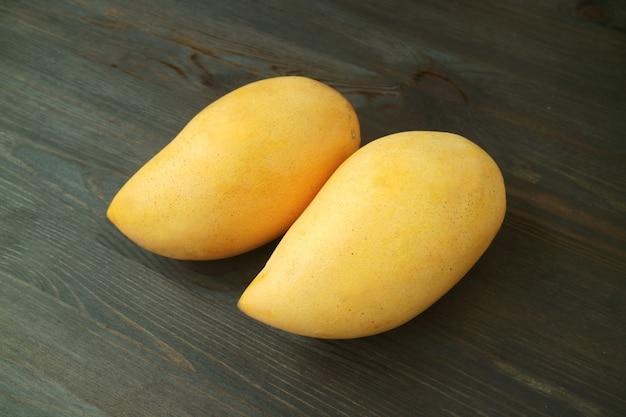 Paare thailändischer frischer reifer nam dok mai mangoes isolated auf dunkelbraunem holztisch