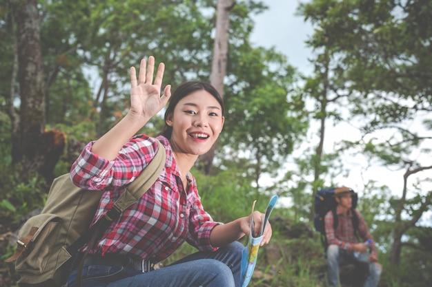 Paare trinken wasser und sehen eine karte im tropischen wald zusammen mit rucksäcken im wald. abenteuer, reisen, klettern, wandern.