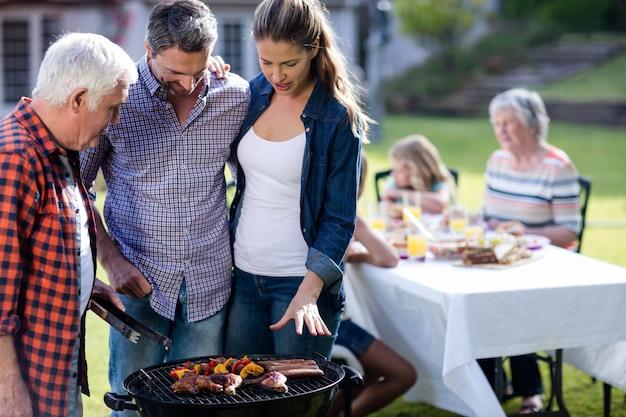 Paare und ein älterer mann am grill grillen das vorbereiten eines grills