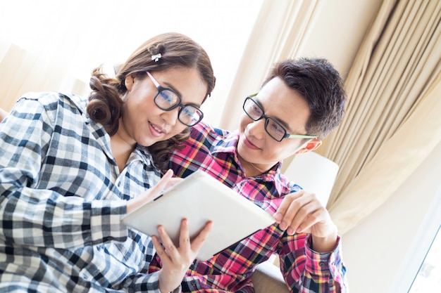 Paare unter verwendung der tablette im wohnzimmer