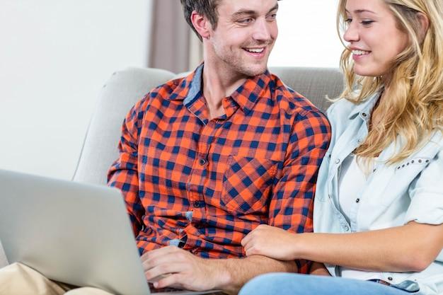 Paare unter verwendung des laptops auf der couch im wohnzimmer