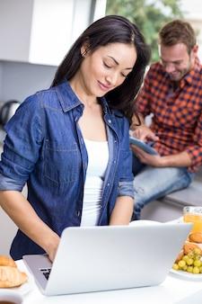 Paare unter verwendung des laptops und der digitalen tablette in der küche