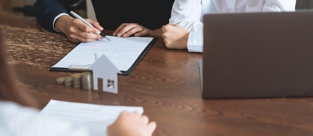 Paare unterzeichneten einen vertrag, um ein haus vom makler zu kaufen.