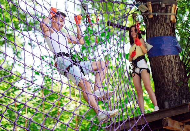 Paare verbringen ihre freizeit in einem hochseilgarten. mann und frau im klettern beschäftigt,