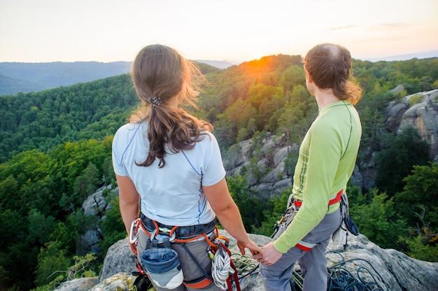Paare von den bergsteigern, die schöne naturansicht stillstehen und genießen