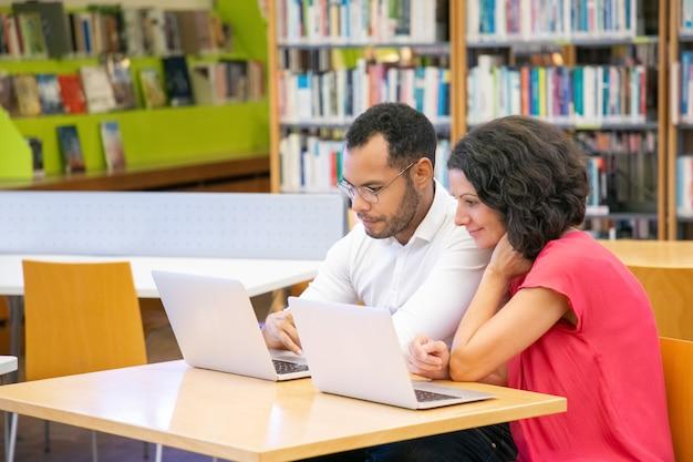 Paare von den erwachsenen studenten, die akademische forschung tun und besprechen